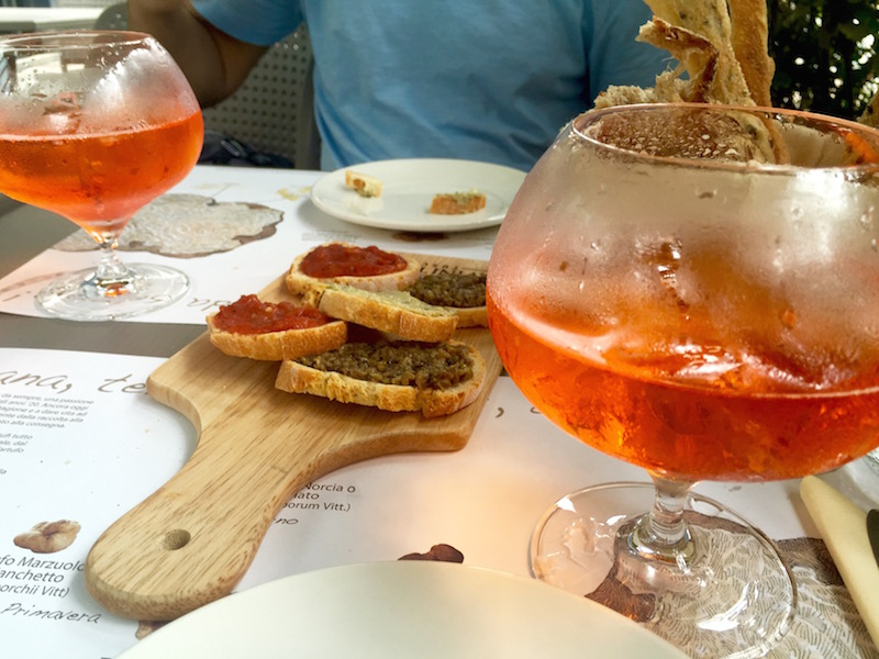 Assorted bruschetta with truffles and a side of aperol spritz
