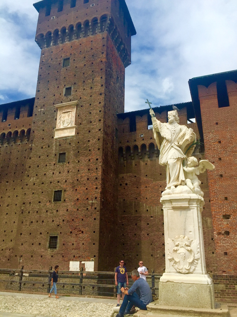 Tourists relax by a statue in the grounds of Castello Sforzesco